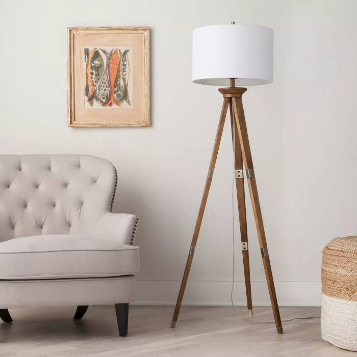 The tripod lamp with wooden legs and brass accents in a living room