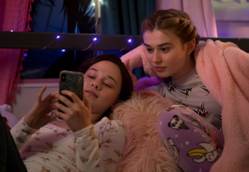Erin looks at her phone with her friend beside her