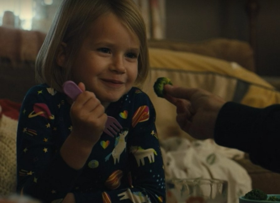 Katie's daughter smiles as her grandmother holds a piece of broccoli in front of her face