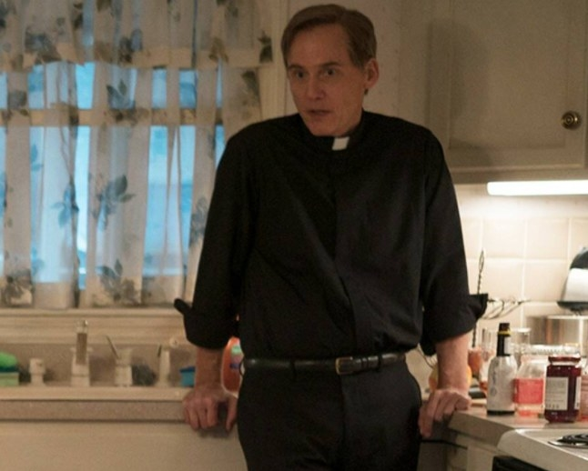 Father Hastings leans on the kitchen counter