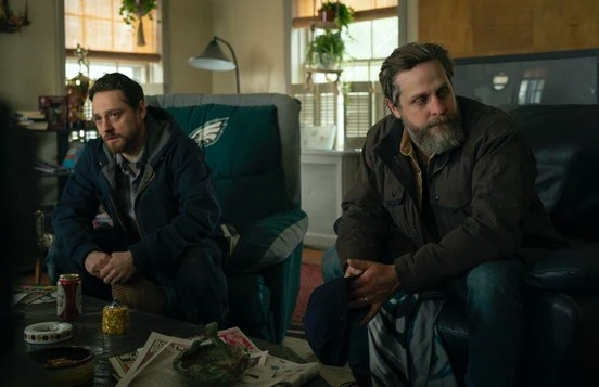 Billy and John Ross sit on chairs in a messy living room