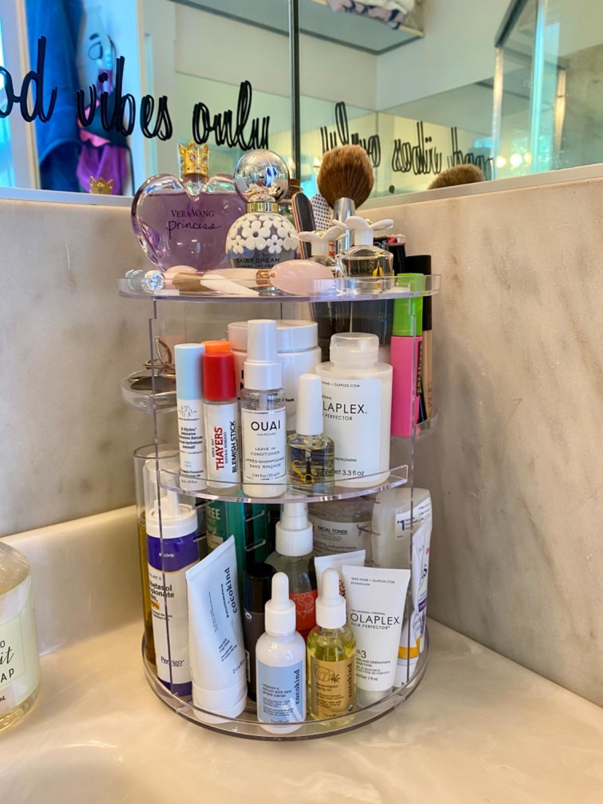 A reviewer photo of a clear rotating plastic makeup organizer with skincare and perfume on it