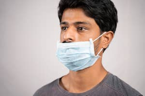 A man wearing a surgical mask incorrectly, below his nose