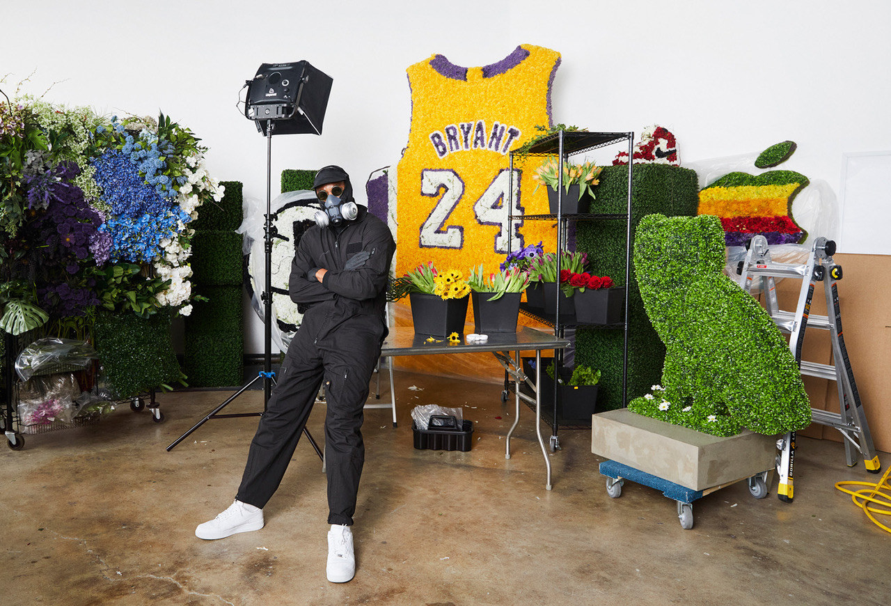 A man wearing coveralls, sunglasses, and a gas mask stands among some floral sculptures, including the Drake OVO owl logo, Kobe Bryant's Lakers jersey, and the original Apple company logo
