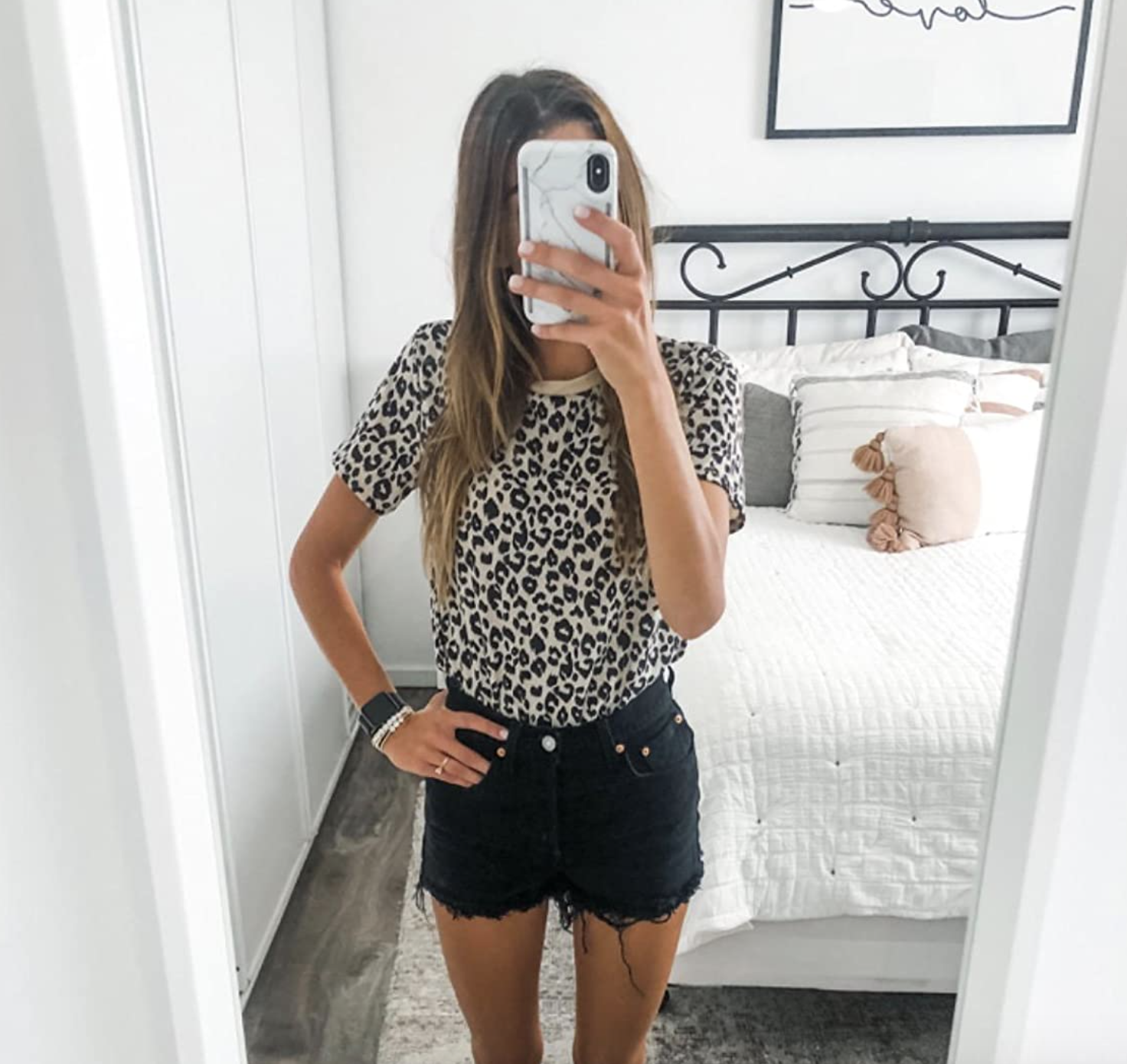 reviewer wearing top tucked into black denim shorts