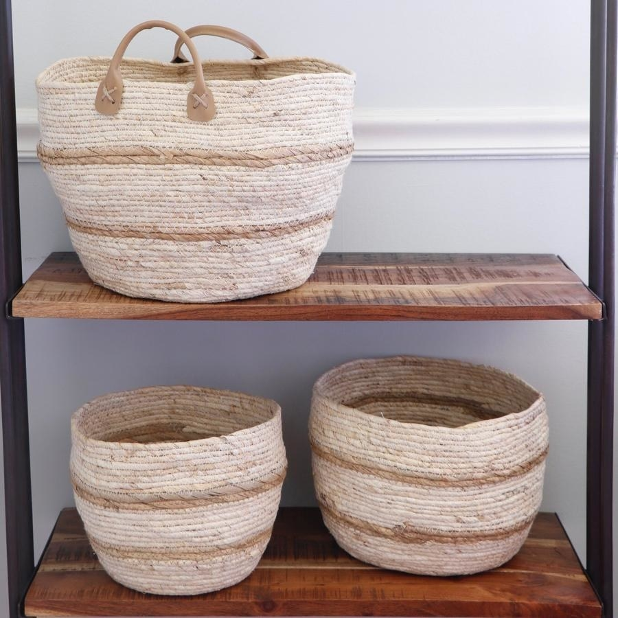 three empty woven baskets on a bookshelf