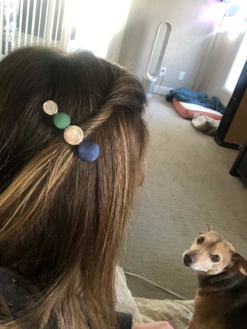 reviewer wearing blue, white, gold and pink clip wit round stones