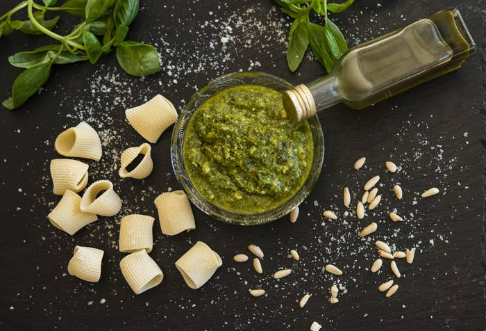 A. bowl of pesto next to some dry pasta shells and pine nuts