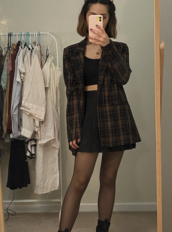 different reviewer wearing with tights, crop top, and blazer