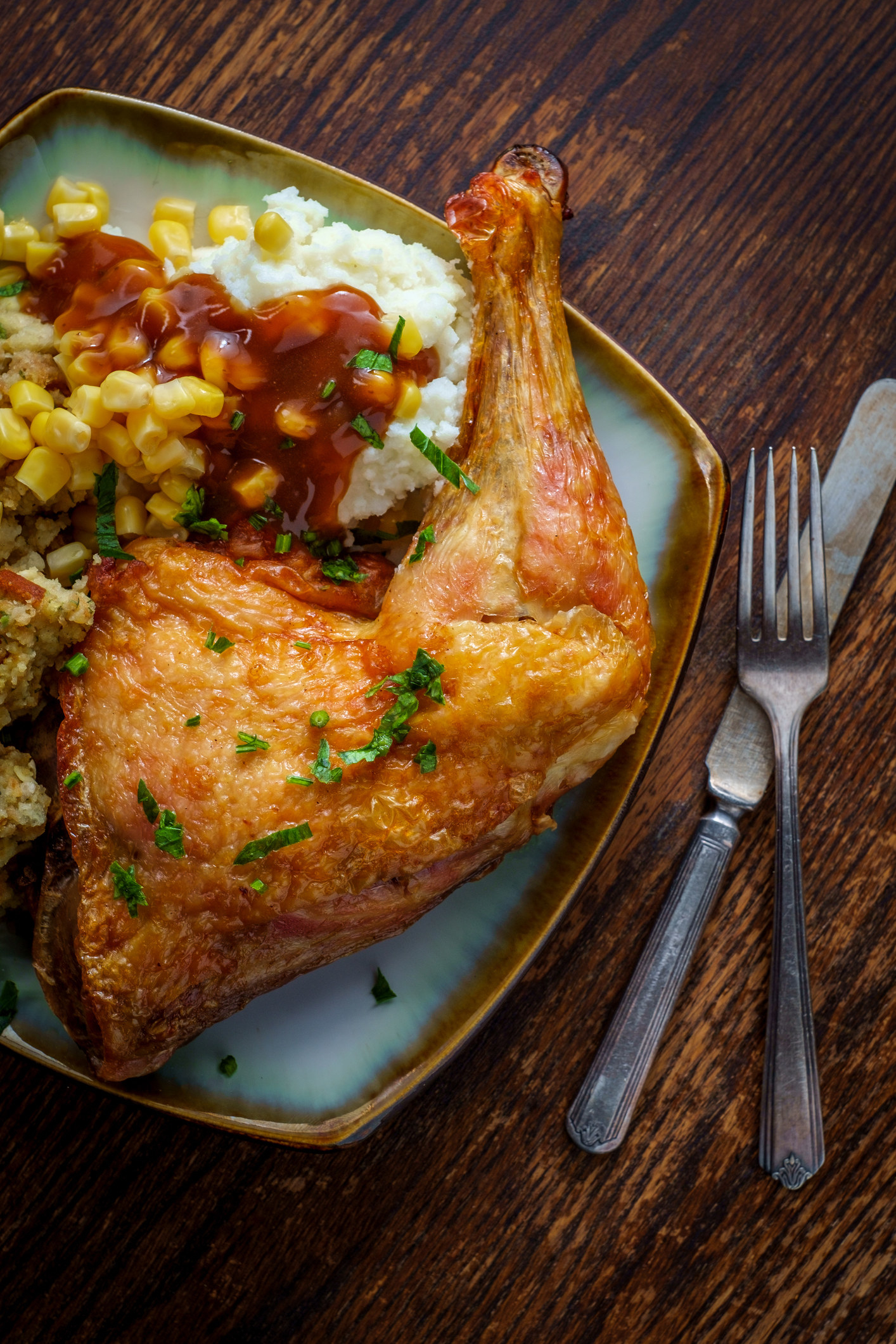 A crispy chicken leg on a plate with mashed potatoes and corn