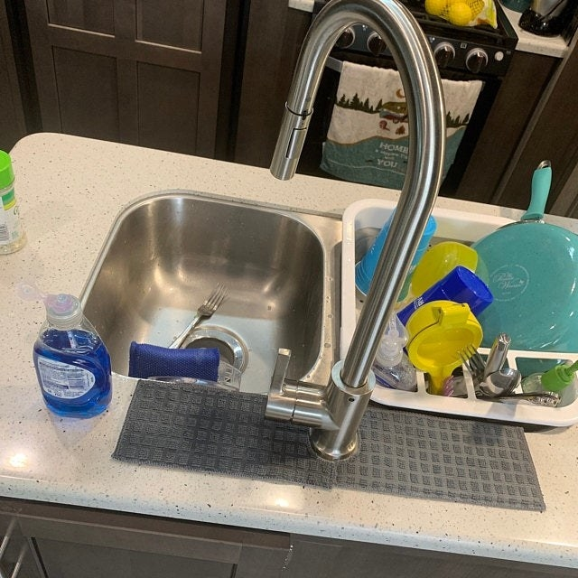 reviewer's faucet with a narrow, grey towel-like mat extending several inches to either side
