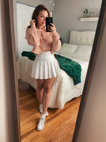 reviewer wearing white skirt with hoodie and Converse