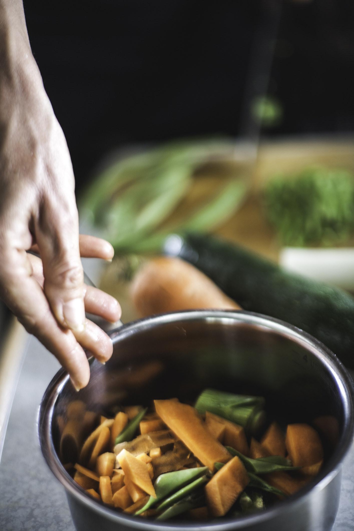 Adding veggie scraps to a pot for stock