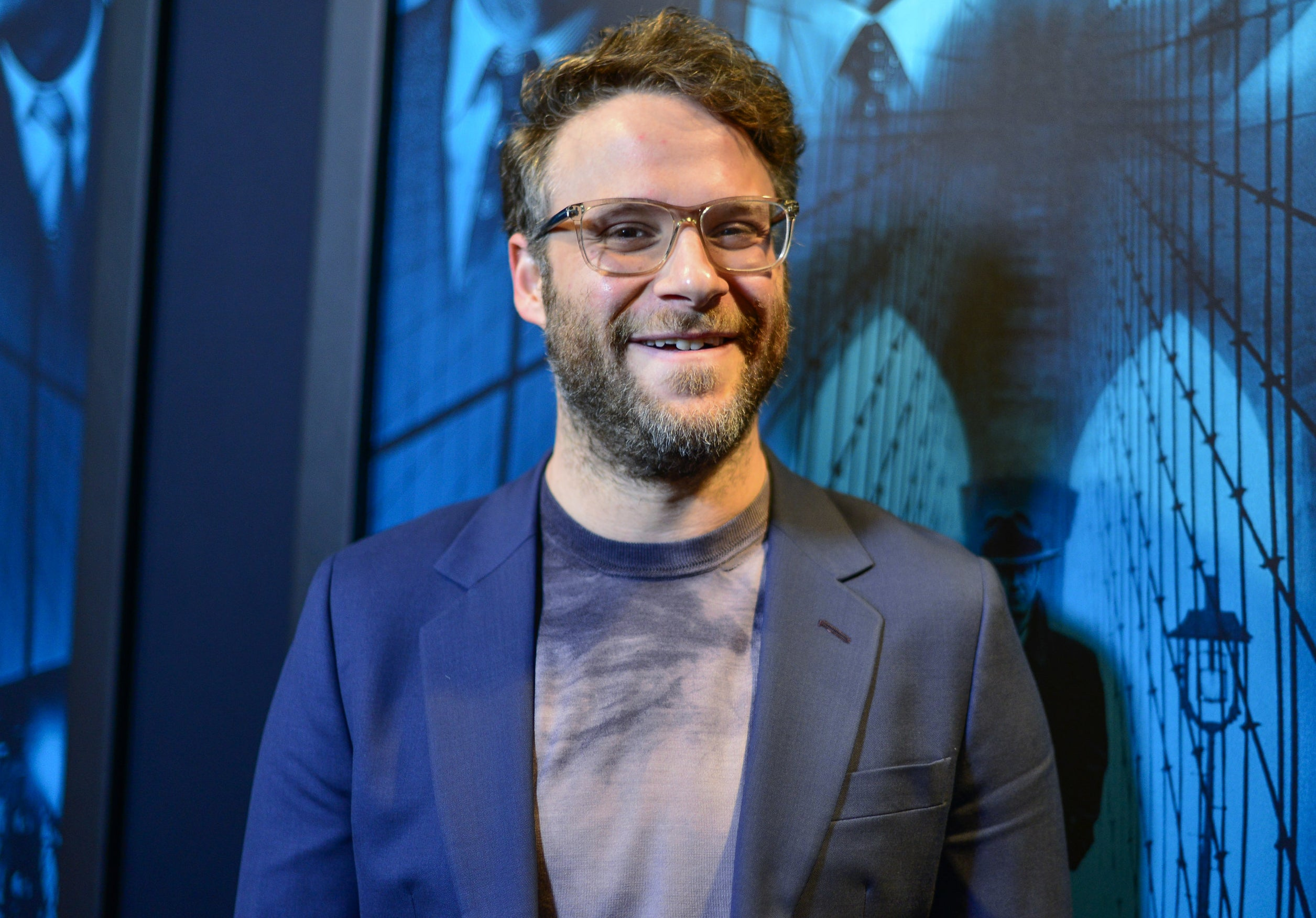 Seth smiles while wearing a blue blazer and t-shirt