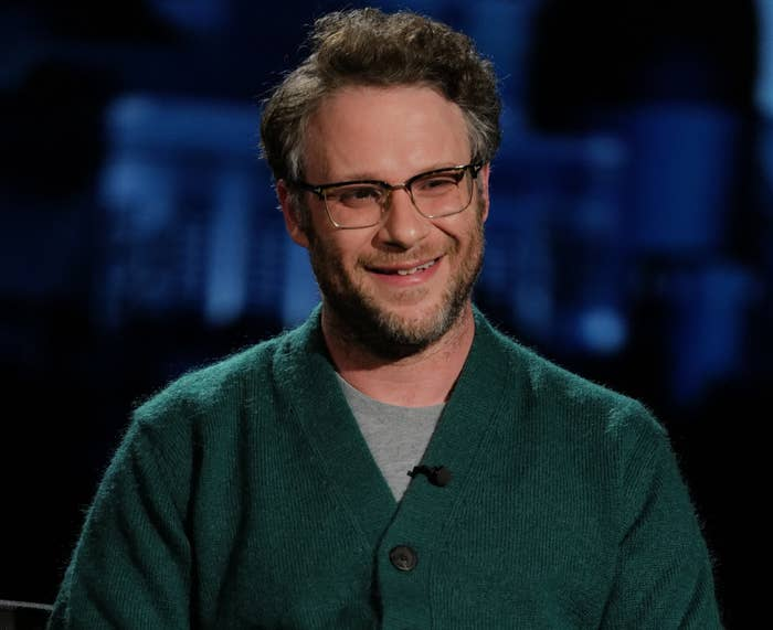 Seth smiles while wearing a green cardigan