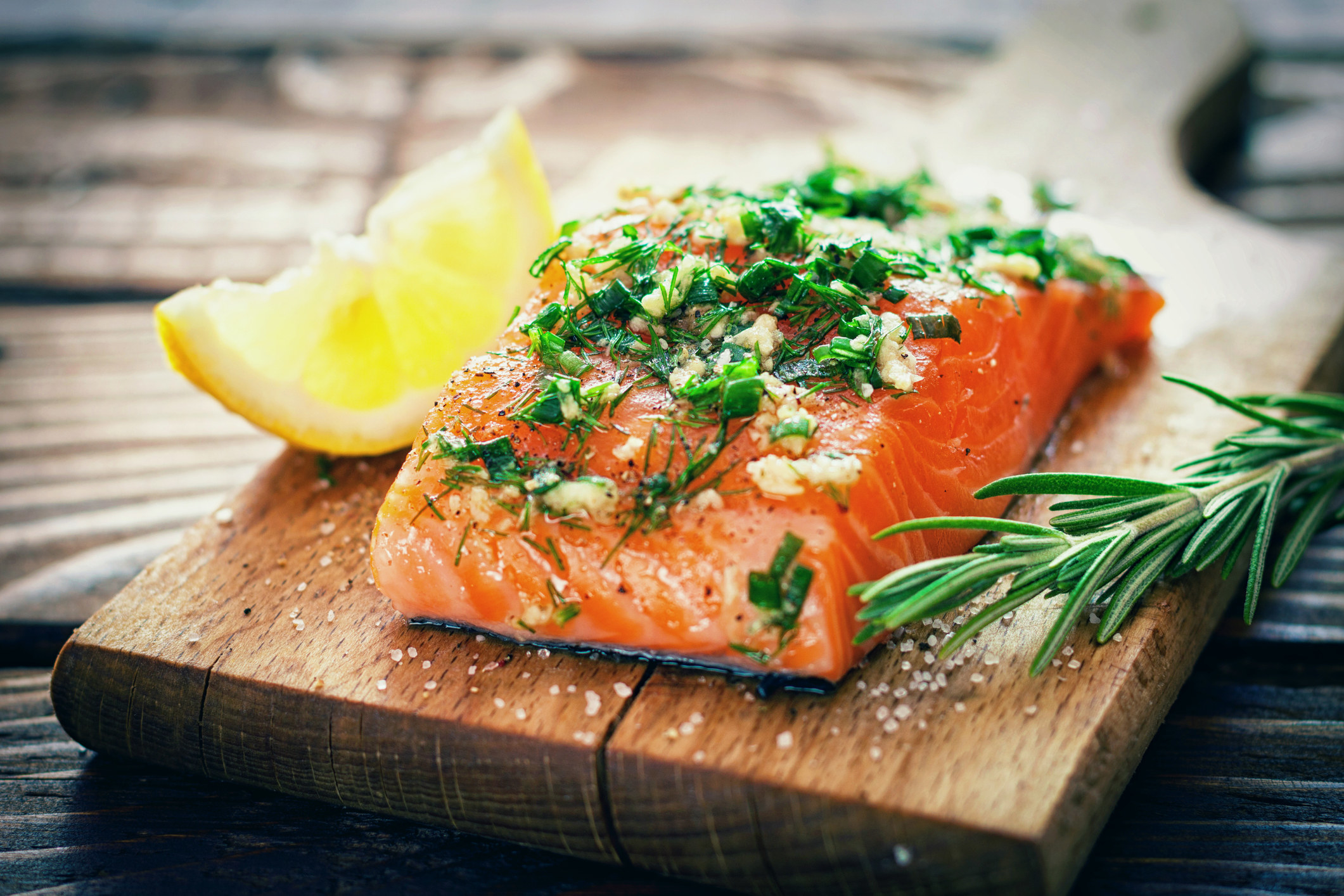 A piece of salmon topped with fresh herbs and spices.