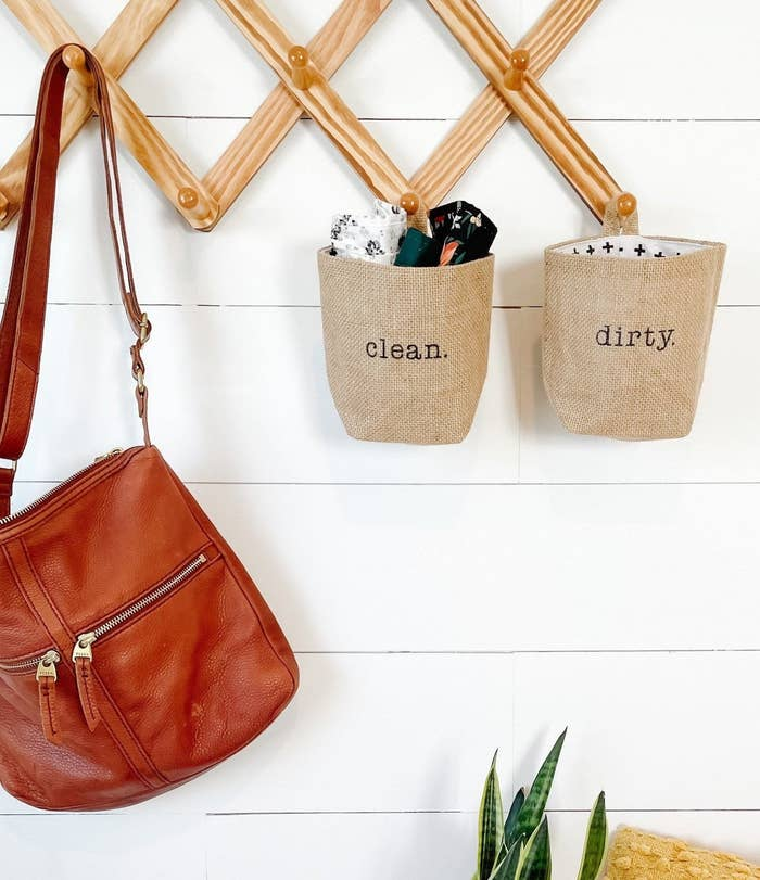 """face mask pouches that say """"clean"""" and """"dirty"""" hanging on wall hooks"""