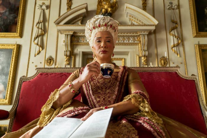 Queen Charlotte sitting, sipping tea, and reading