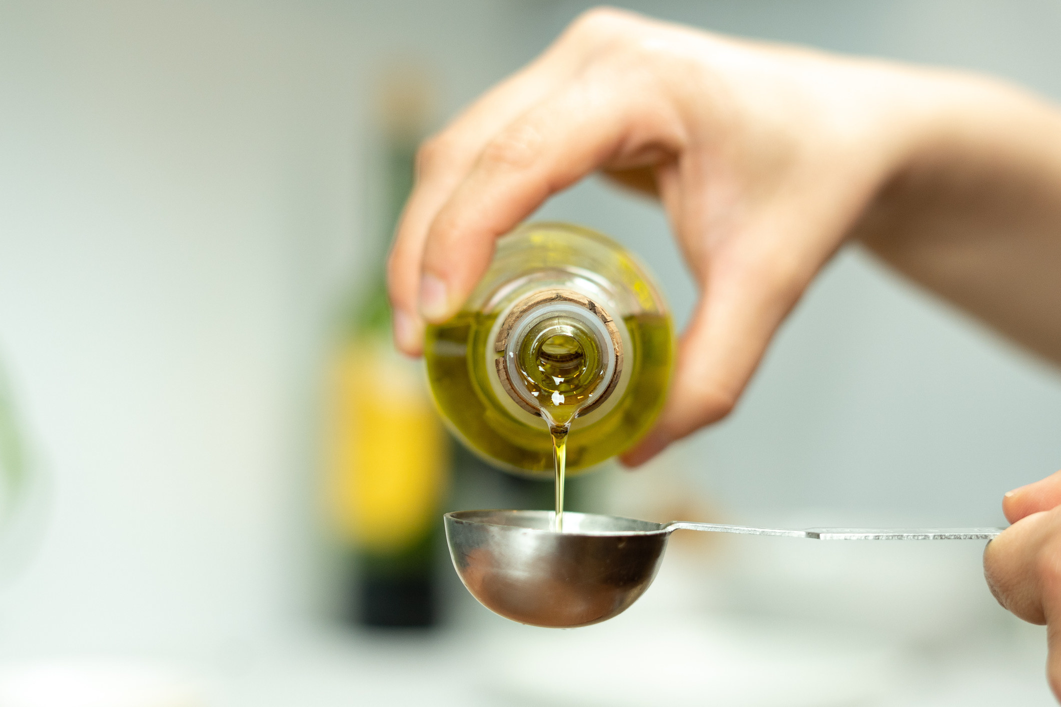 Measuring olive oil into a spoon