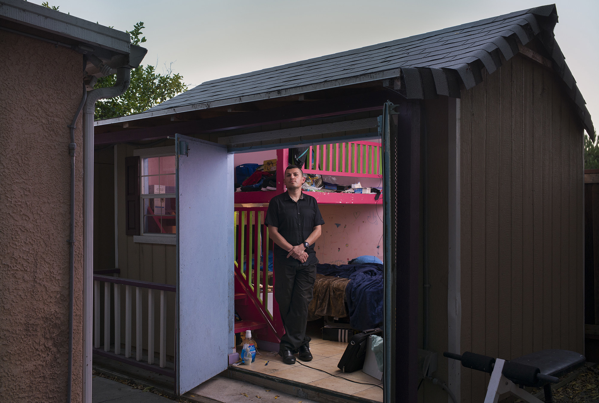 A man stands in the doorway of a small home where he lives