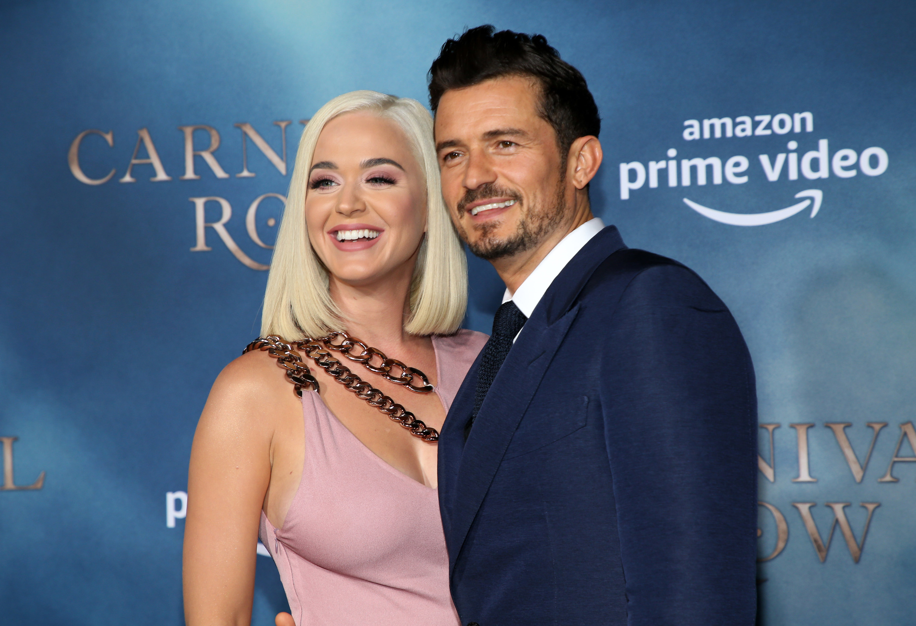 Katy and Orlando smile while posing on a red carpet