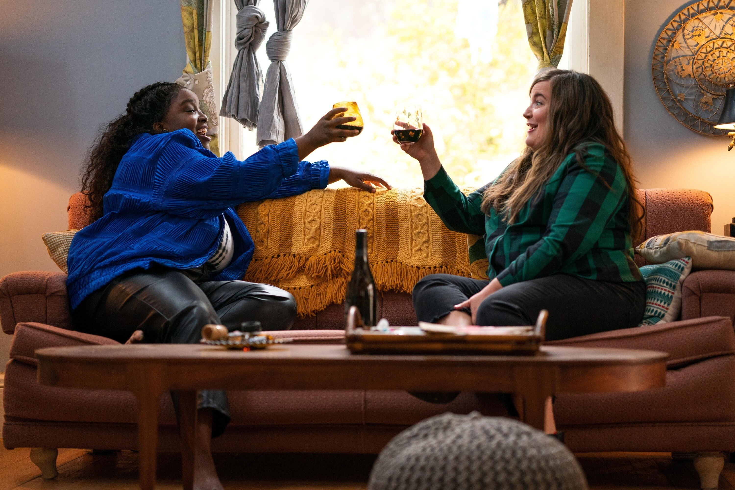 Lolly Adefope and Aidy Bryant raise glasses to each other