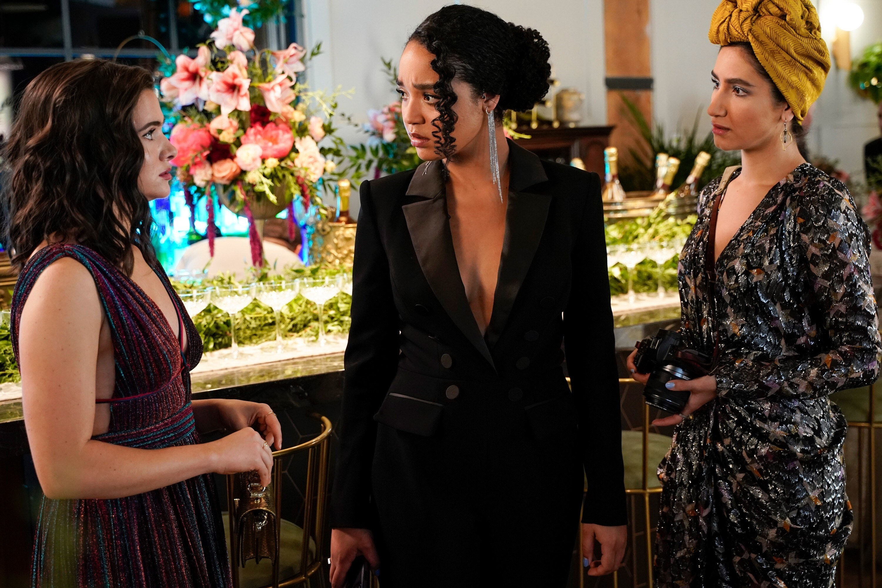 Katie Stevens, Aisha Dee, and Nikohl Boosheri at a dinner party