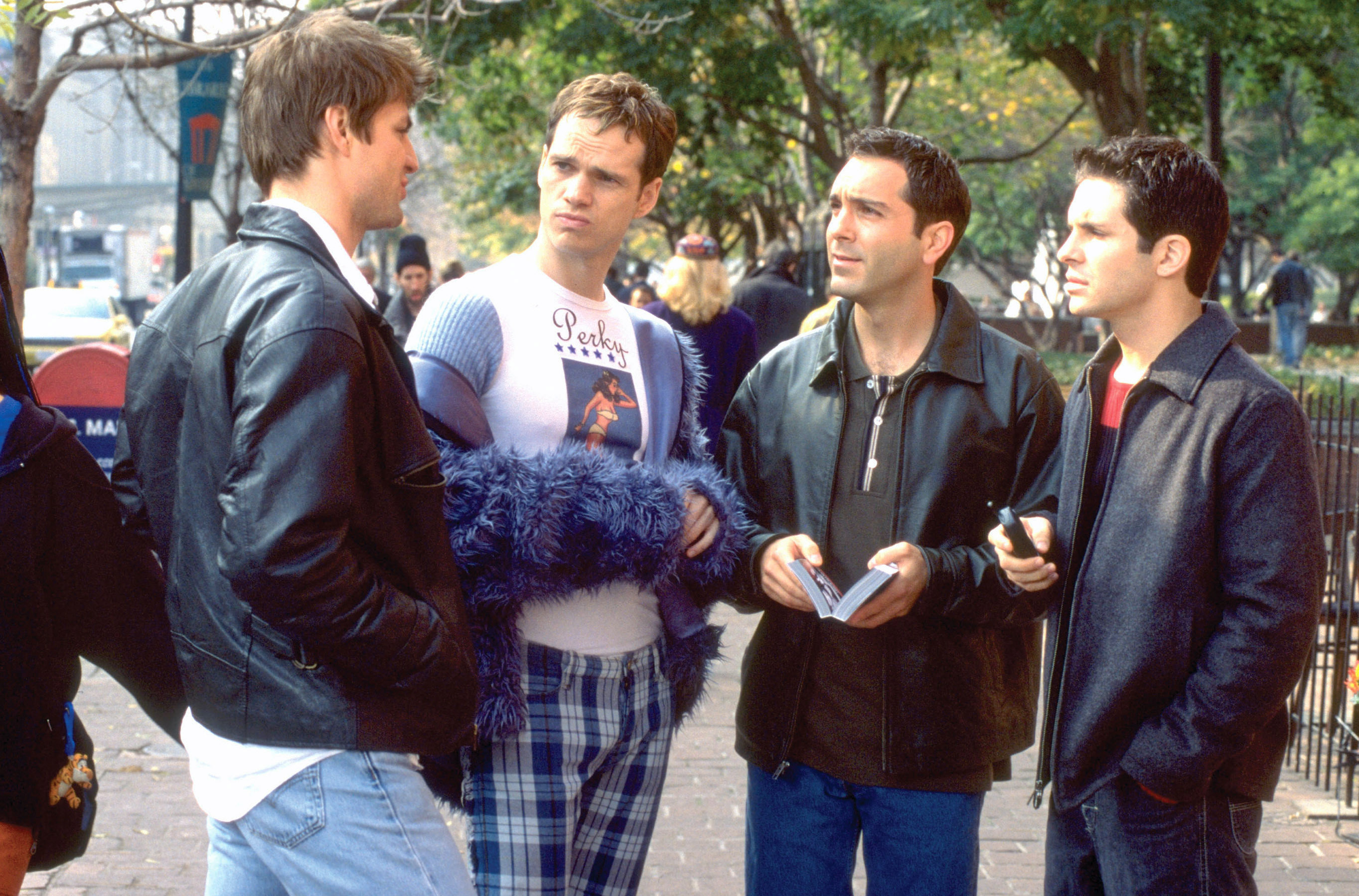 Gale Harold, Peter Paige, Scott Lowell, and Hal Sparks stand in a park