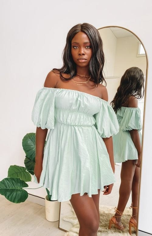 A model wearing the off-the-shoulder dress in a pastel-mint color
