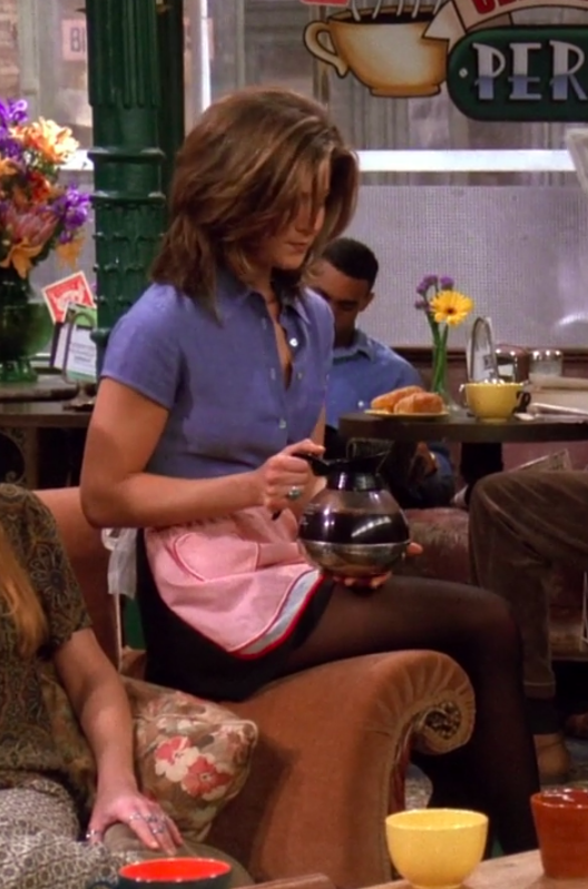Rachel wearing a short-sleeve button-up, an apron, a miniskirt, and tights