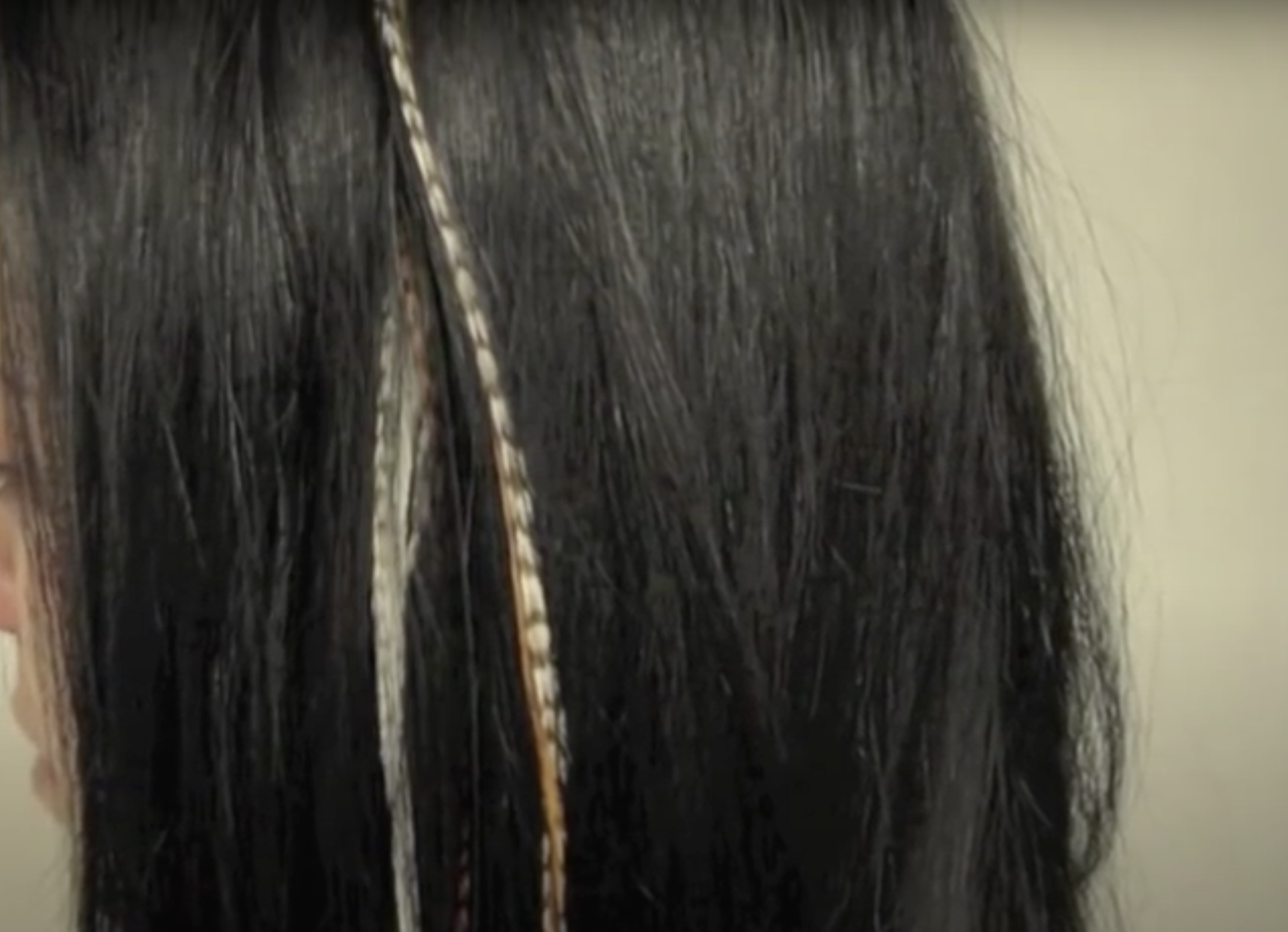 A person with two feather hair extensions