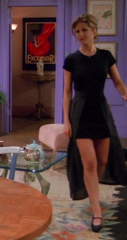 Rachel wearing a short-sleeve shirt and a miniskirt with an attached cape