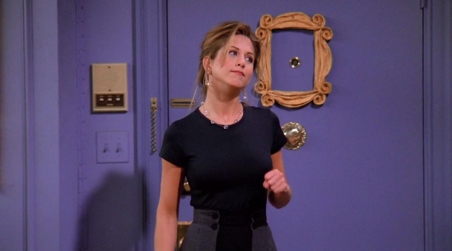 Rachel wearing a short-sleeve shirt and a mini skirt with an attached cape