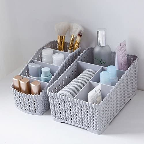 A grey-coloured sectioned organiser with items in it