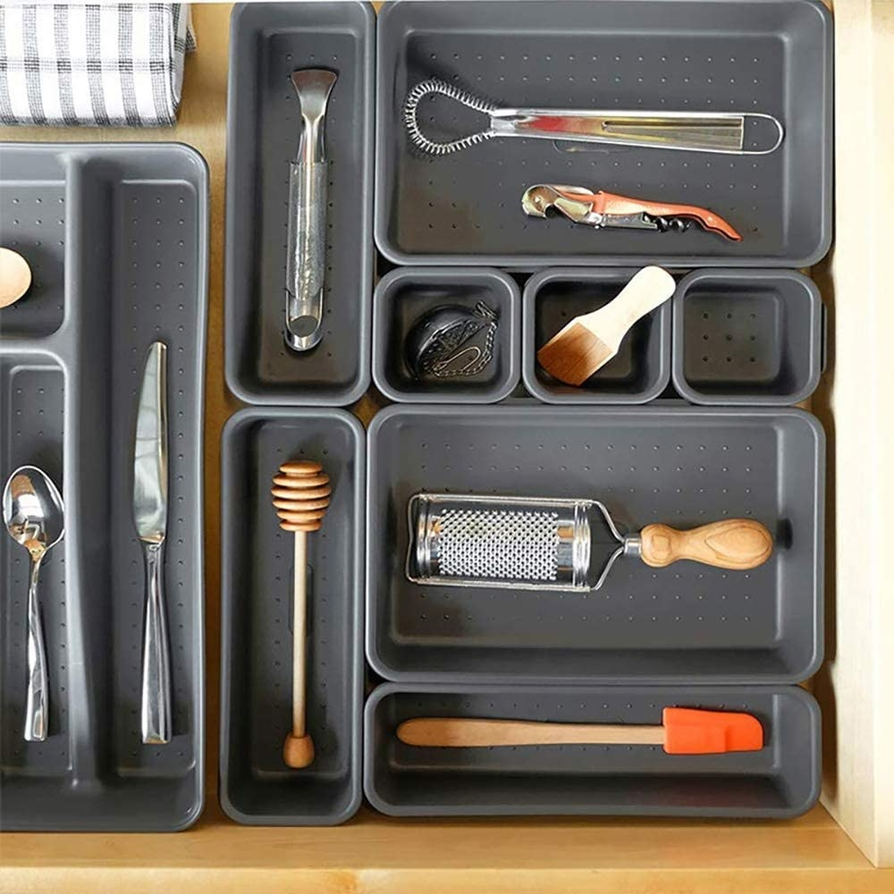 A set of interlocking bins arranged inside a drawer with items stored in them.