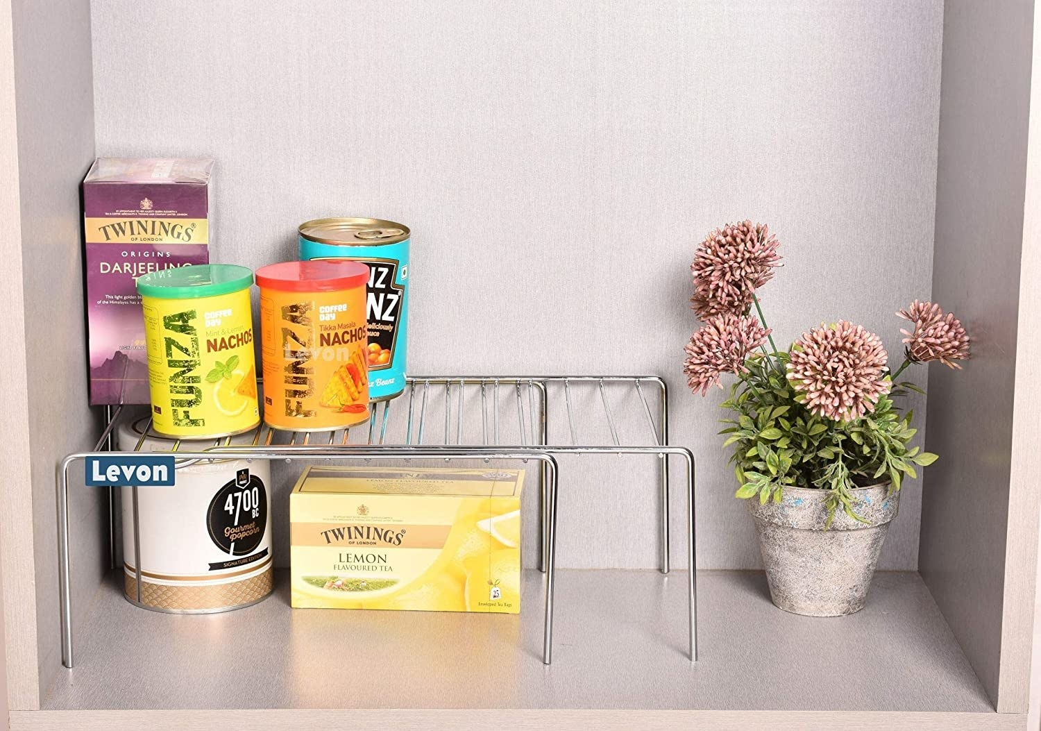 An expandable rack with food items on it next to a flower pot.