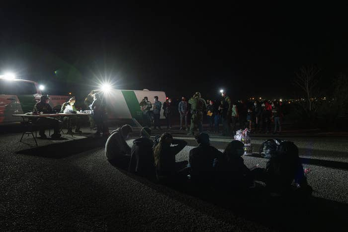 Border Patrol agents sit at a table in front of their vehicles while asylum-seekers sit on the pavement waiting to be processed