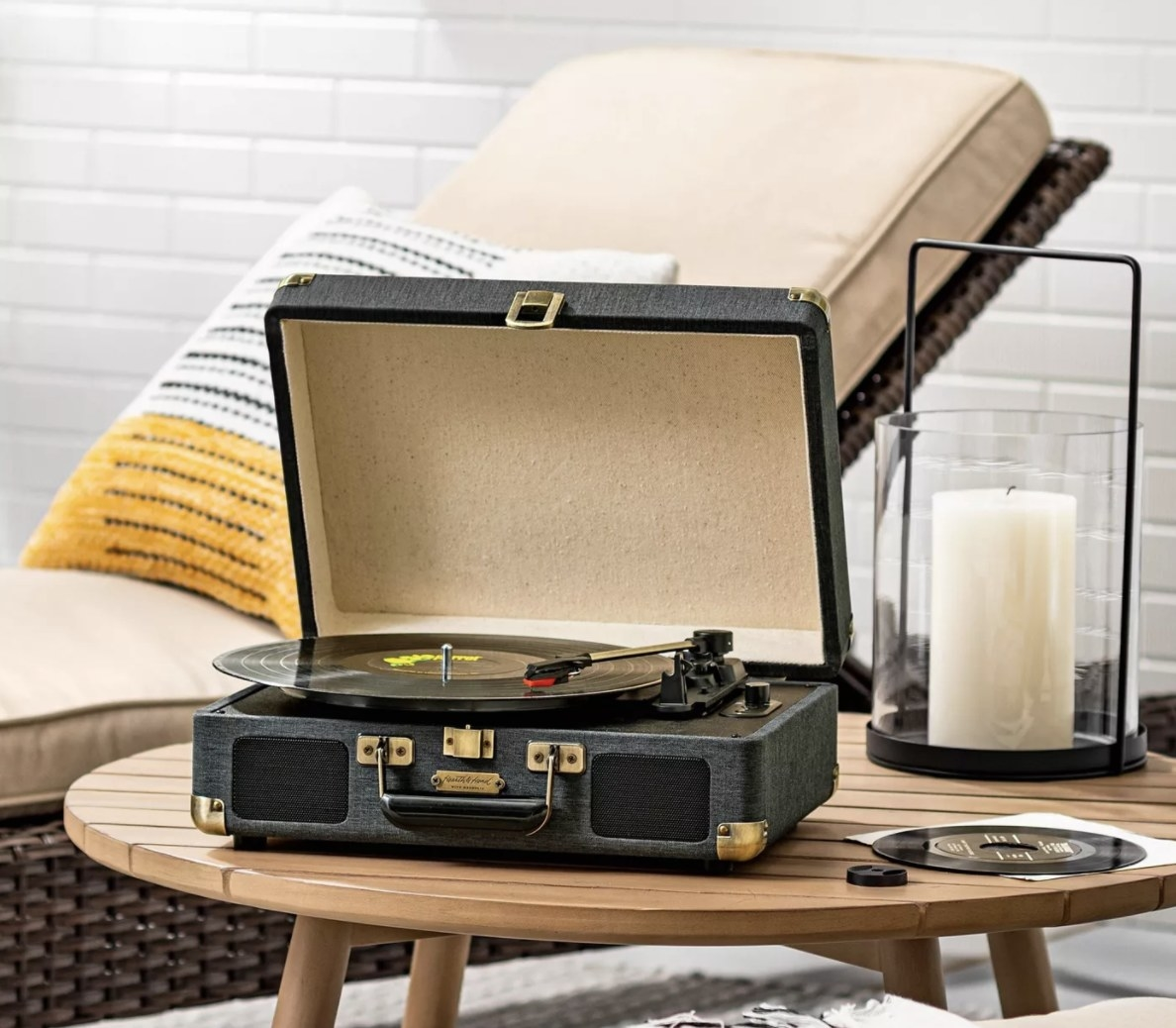 The black suitcase has a record player on the inside and is set atop a wooden table