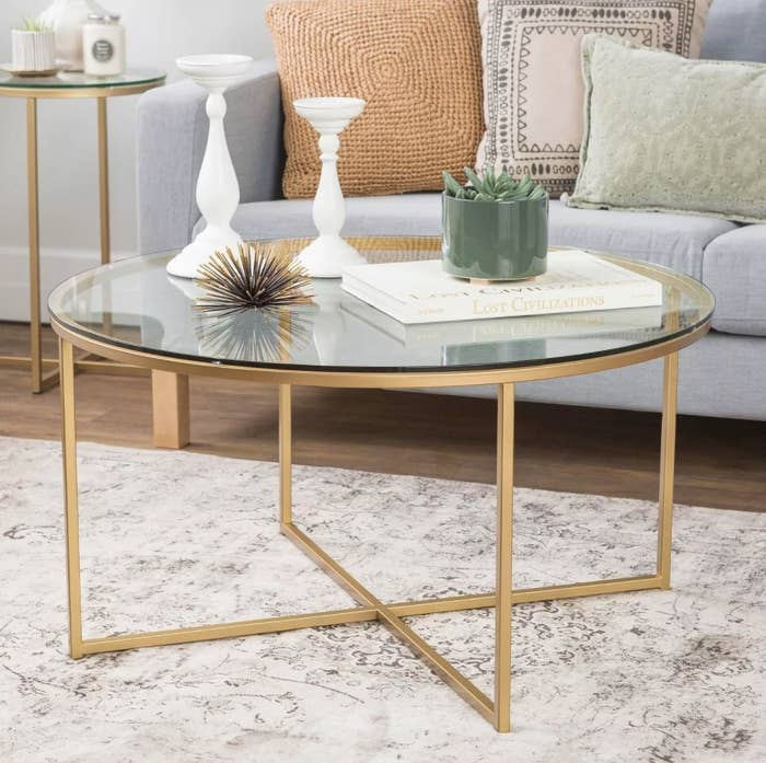 A round coffee table with glass top and brass/gold criss-cross legs