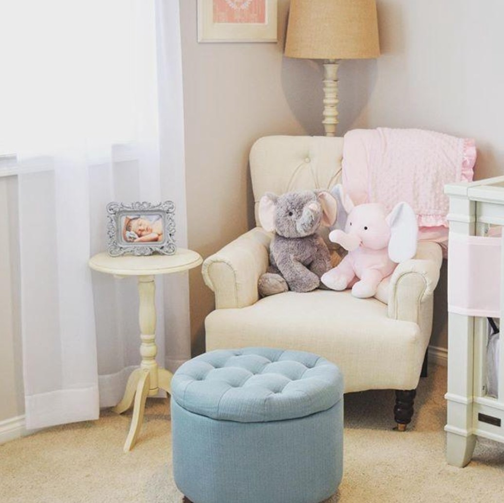 A light blue tufted storage ottoman with wooden legs