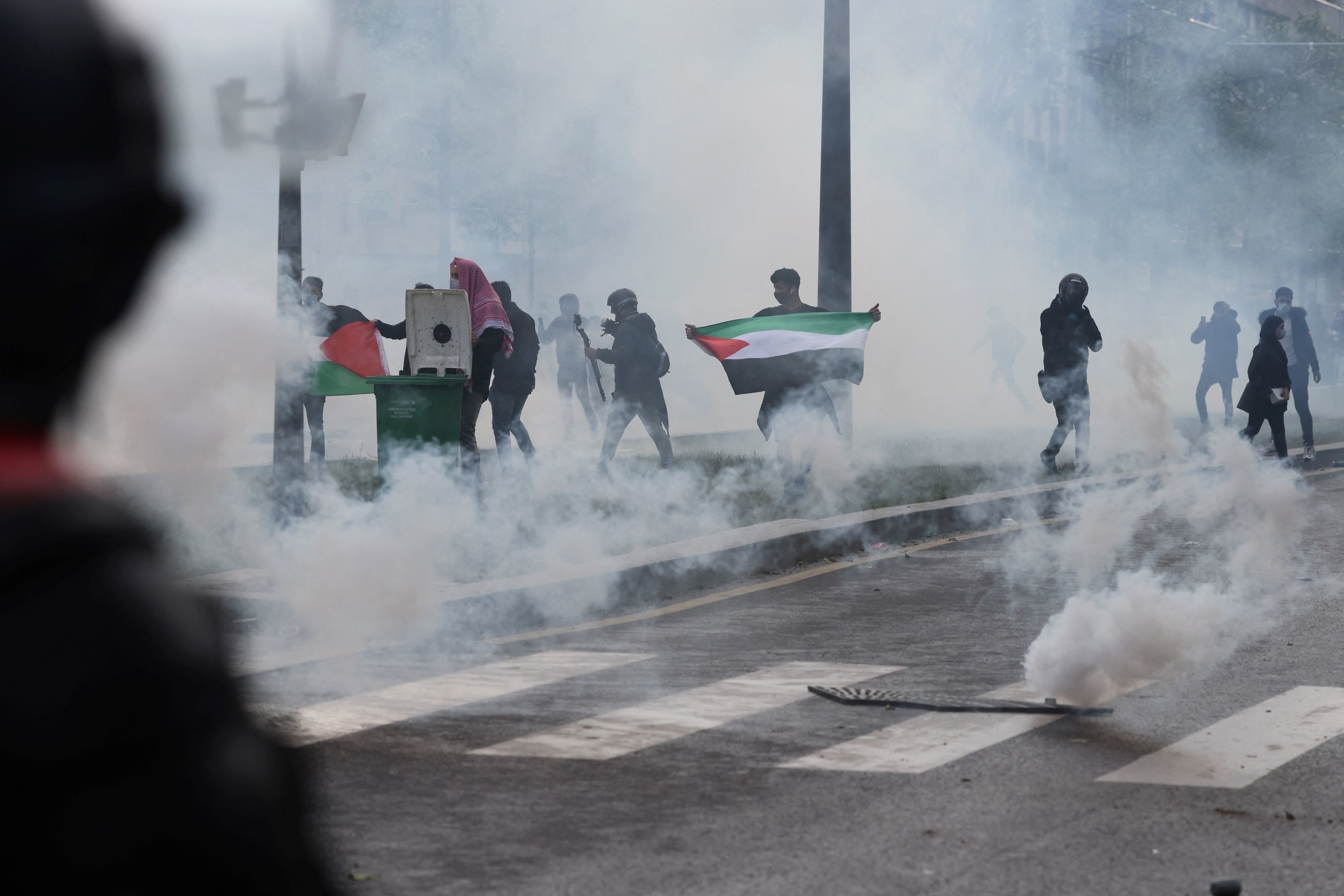 Protesters, including one holding the Palestinian flag, amid tear gas