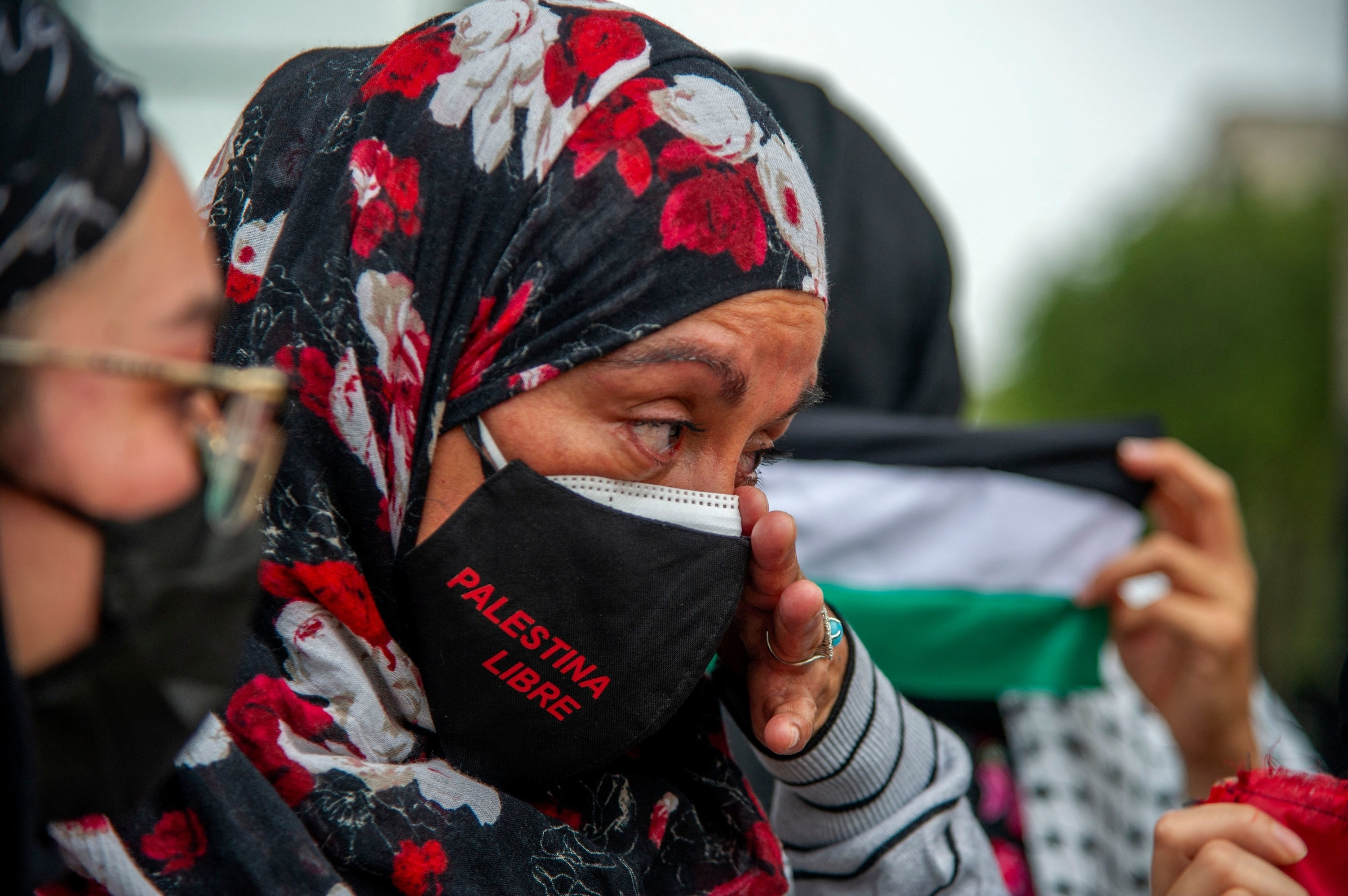 """A woman wearing a """"Palestina libre"""" mask wipes a tear from her eye"""