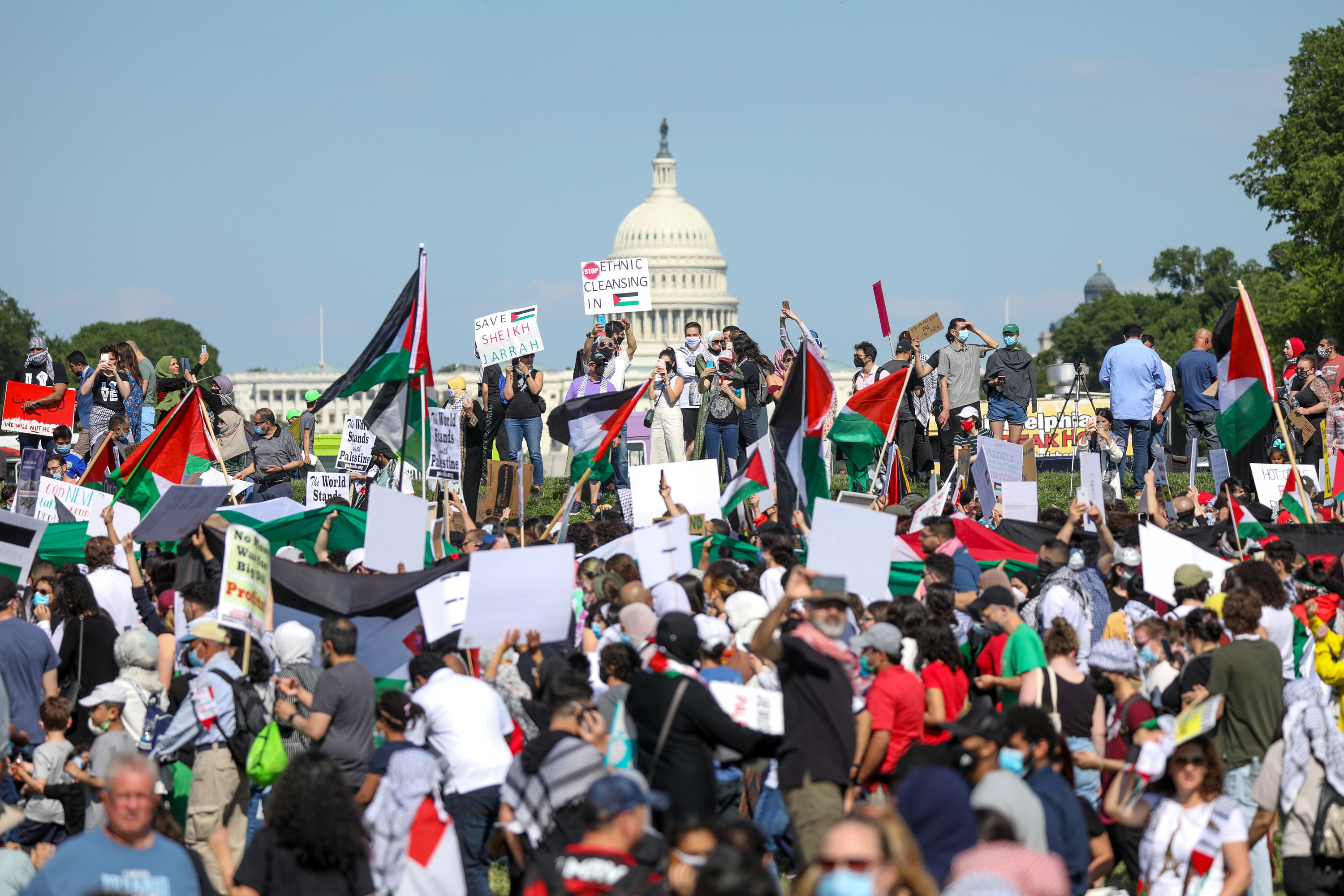 Protesters holding up Palestinian flags and holding up signs gather