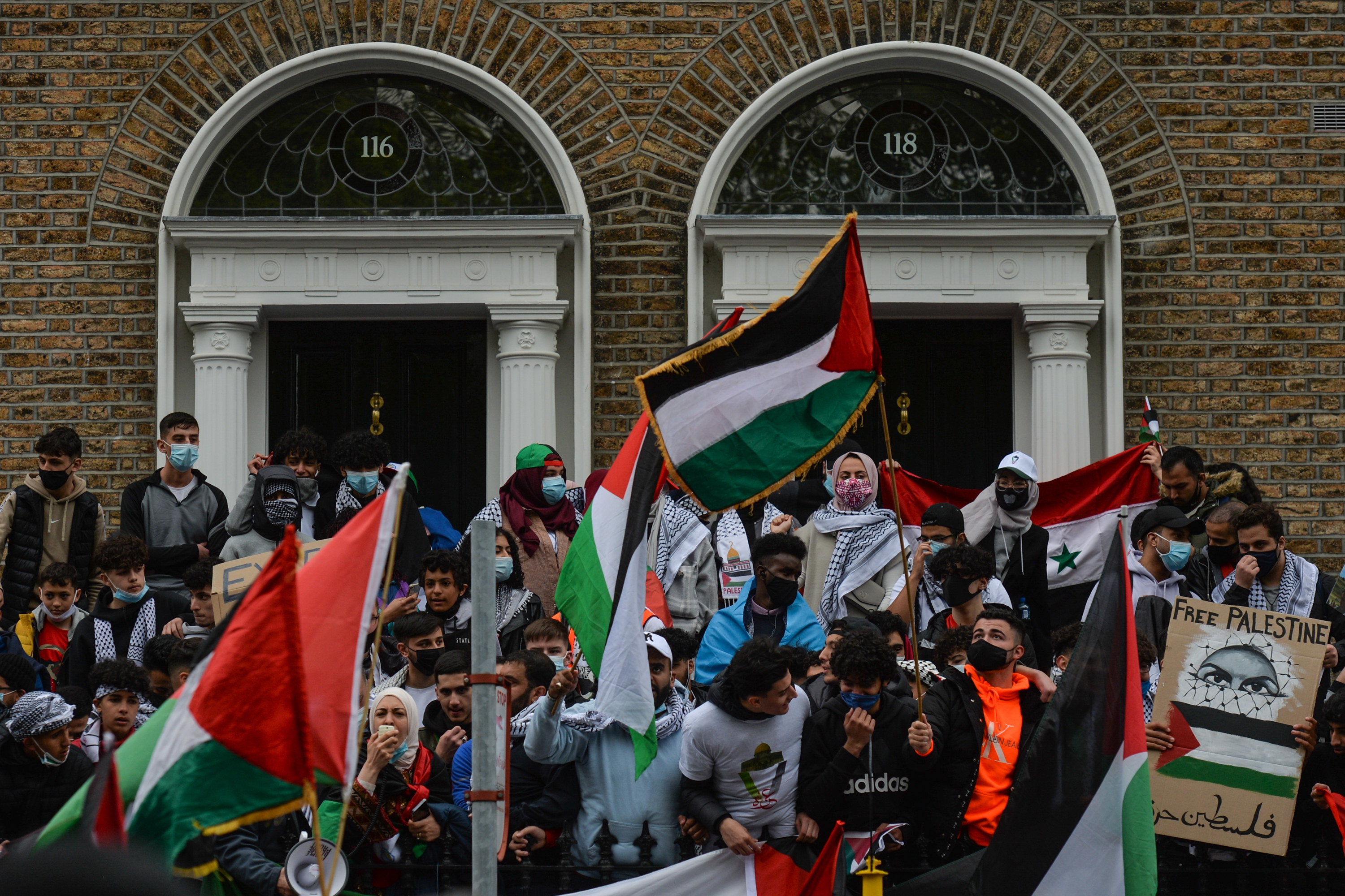 """Protesters, many wearing masks, hold up Palestinian and other flags and a """"Free Palestine"""" sign"""