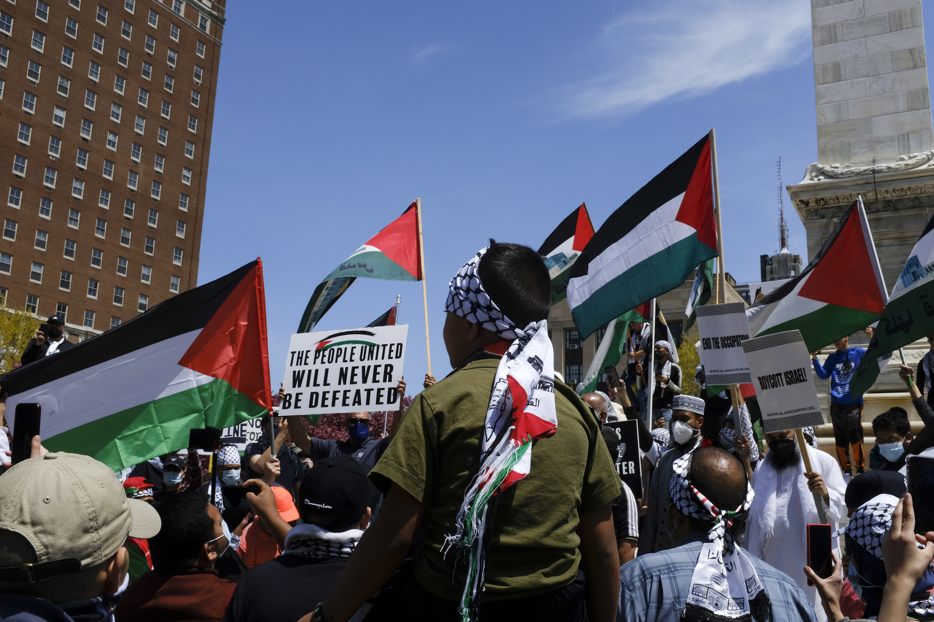 """Protesters wave Palestinian flags and a sign reading, """"The people united will never be defeated"""""""