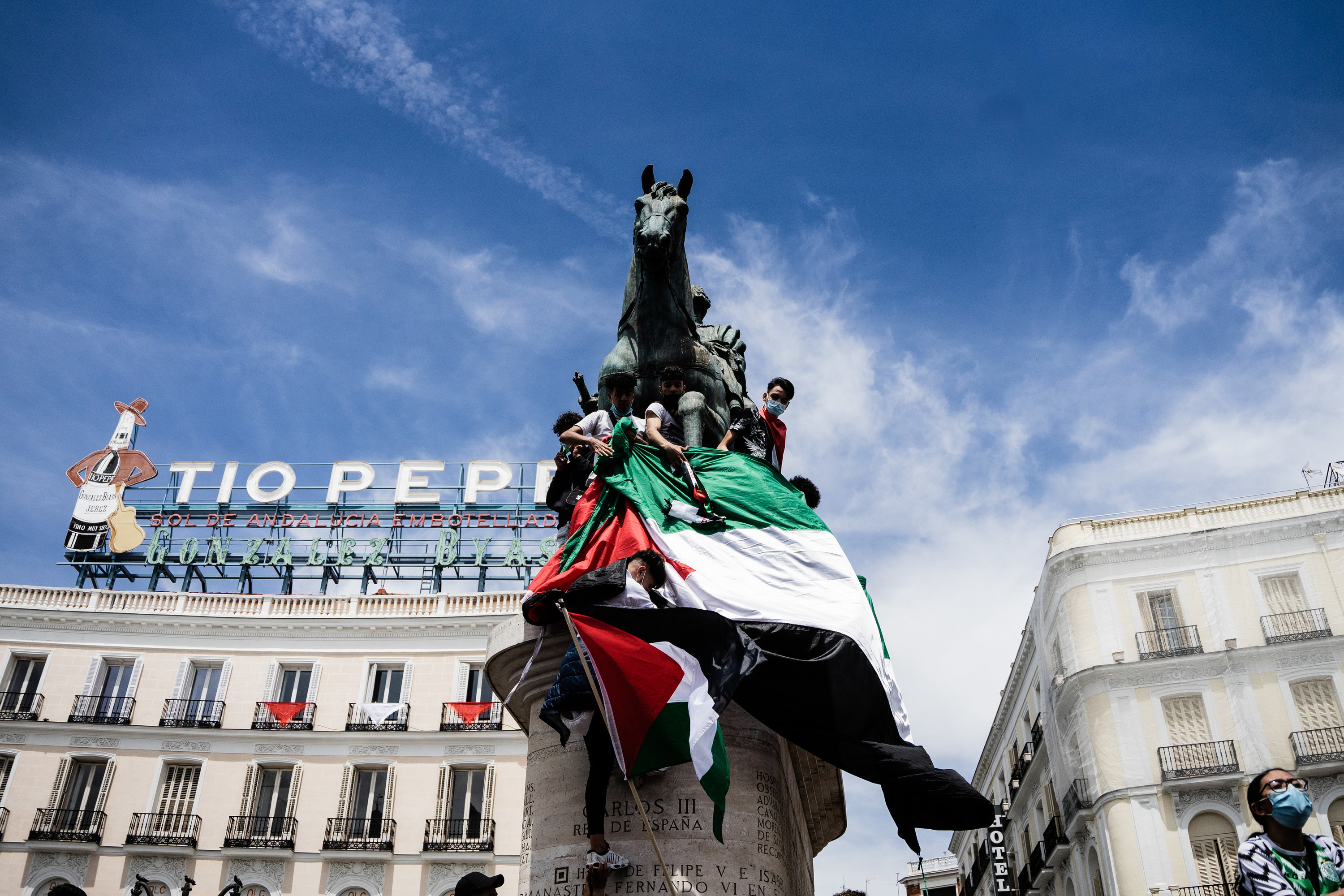 Protesters on the King Carlos III statue in Puerta del Sol hold up the Palestinian flag