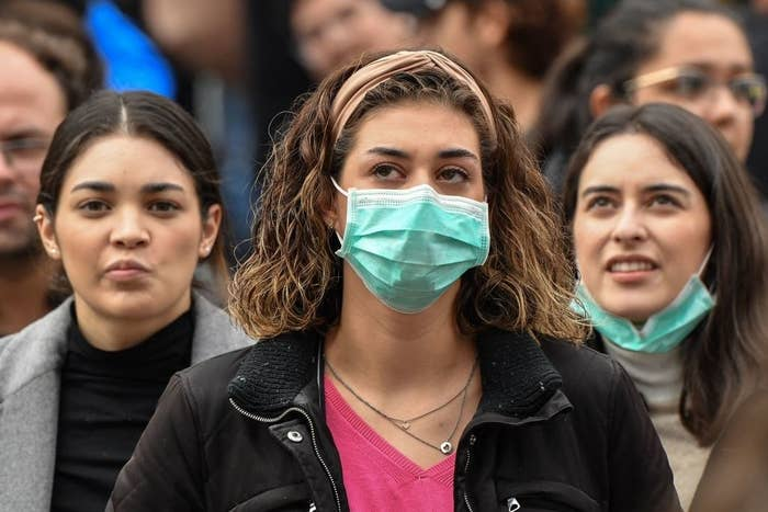 Three women in a crowd, one not wearing a mask, one wearing a surgical mask, and one wearing a surgical mask below her chin