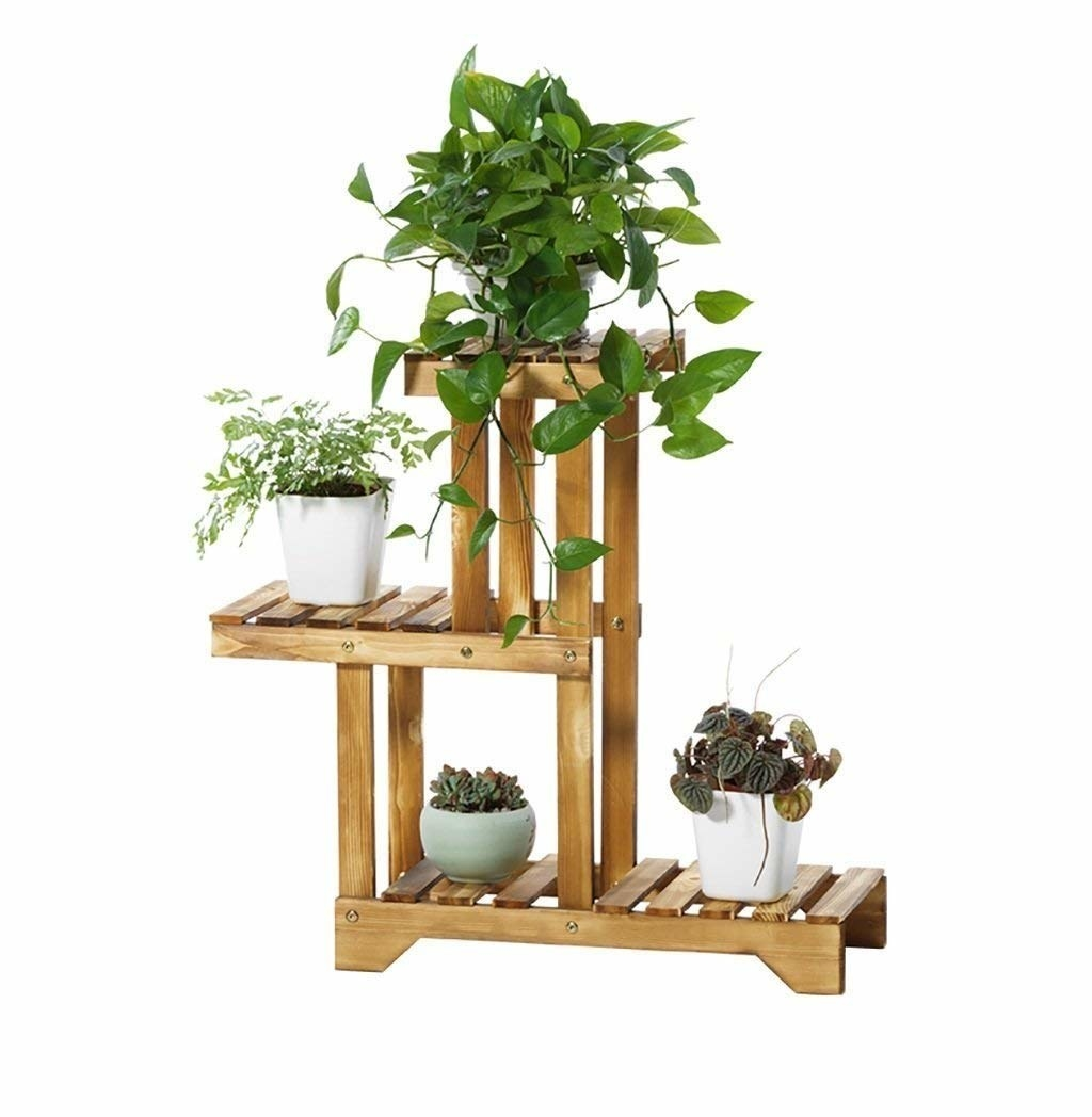 Three tier wooden plant stand with planters on each tier