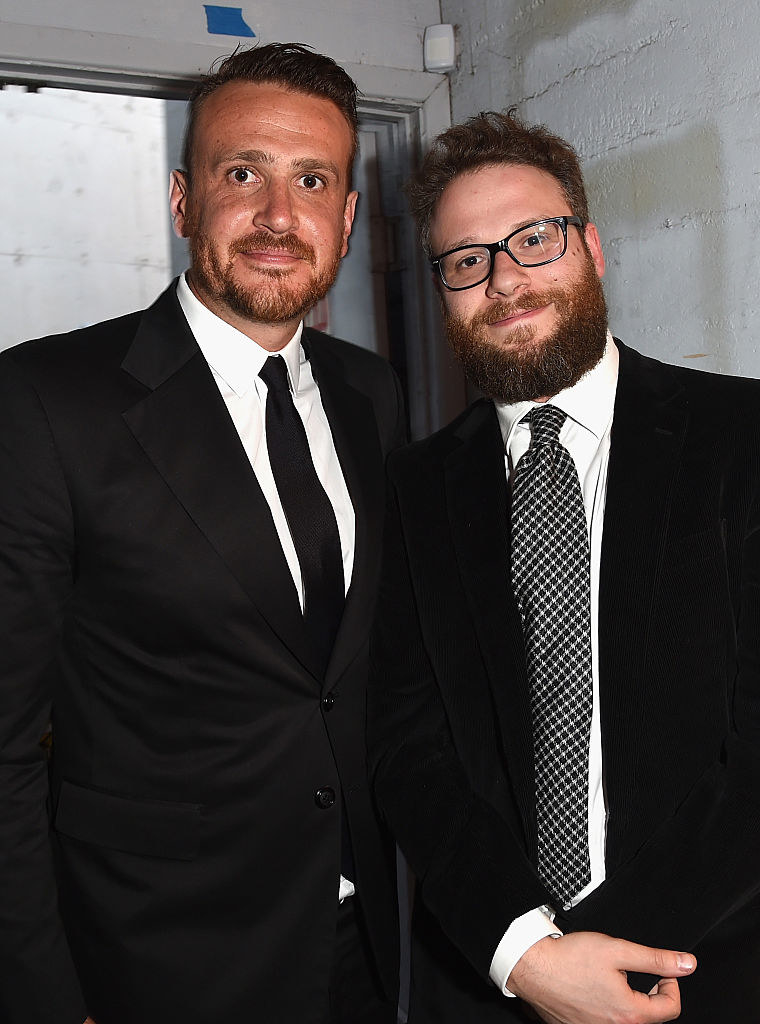 Jason and Seth, both wearing suits, standing close together
