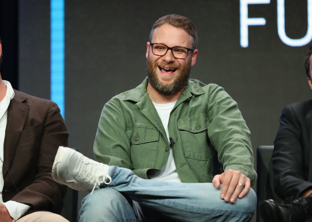 Seth, dressed casually, sitting on a panel, and laughing, with one foot resting on the opposite knee